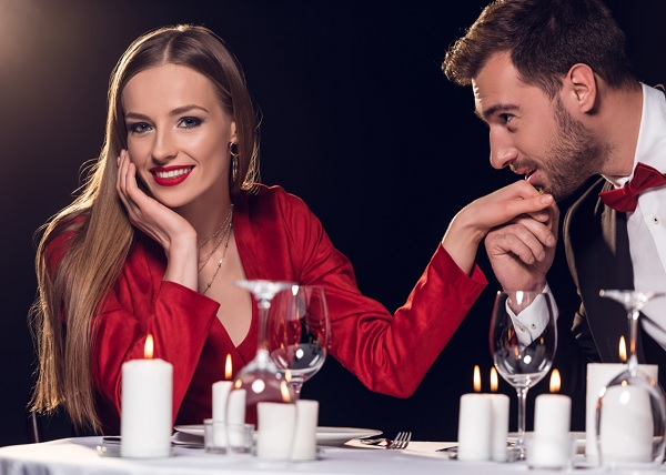 Man kissing a woman's hand during a date in a restaurant.