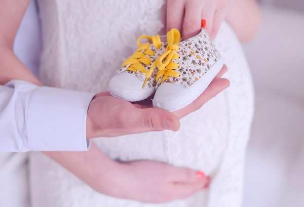 IVF in Russia, baby shoes and mother expecting the child.